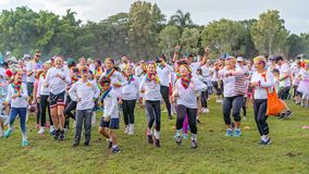 Crowd Warming Up Prior To Color Frenzy Fun Run. MACKAY. QUEENSLAND, AUSTRALIA - JUNE 2019: Unidentified people splashed with colored power warming up prior to a stock photography