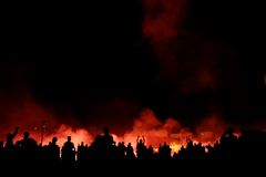 Crowd watching explosions. A crowd of people in front of a firy, explosive background Royalty Free Stock Photography