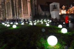 Crowd watching Light bulbs on grass Stock Photography
