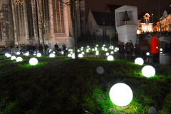 Crowd watching Light bulbs on grass Stock Photography