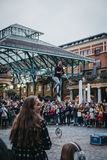 Crowd watching street artist performing in front of Covent Garden Market, London, UK stock image