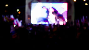 Crowd Waving Flags Watching Concert On Big Screen stock footage