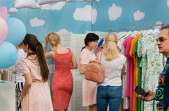 Crowd of women inside cute fashion shop with colorful female clothing Stock Photo