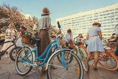 Crowd of women in vintage clothing standing with old bicycles before the start of festival Retro Cruise Stock Images