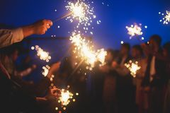 A crowd of young happy people with bengal fire sparklers in their hands during birthday celebration. A crowd of young happy people with sparklers in their hands stock image