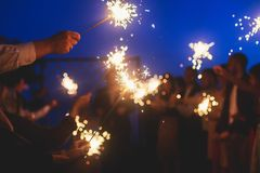 A crowd of young happy people with bengal fire sparklers in their hands during birthday celebration. A crowd of young happy people with sparklers in their hands royalty free stock photos