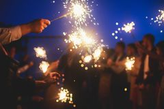A crowd of young happy people with bengal fire sparklers in their hands during birthday celebration. A crowd of young happy people with sparklers in their hands royalty free stock images