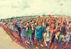 A crowd of young men with painted faces on the colorfest. VOLGOGRAD - JUNE 12: Crowd of young people dancing to the music at the festival of colors at the Stock Images