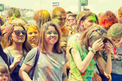 A crowd of young men with painted faces on the colorfest. VOLGOGRAD - JUNE 12: Crowd of young people dancing to the music at the festival of colors at the Royalty Free Stock Photos