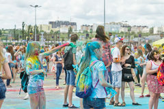 A crowd of young men with painted faces on the colorfest. VOLGOGRAD - JUNE 12: Crowd of young people dancing to the music at the festival of colors at the Royalty Free Stock Images