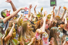 A crowd of young men with painted faces on the colorfest. VOLGOGRAD - JUNE 12: Crowd of young people dancing to the music at the festival of colors at the Stock Photo