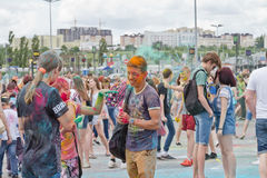 A crowd of young men with painted faces on the colorfest. VOLGOGRAD - JUNE 12: Crowd of young people dancing to the music at the festival of colors at the Royalty Free Stock Photo