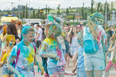 A crowd of young men with painted faces on the colorfest. VOLGOGRAD - JUNE 12: Crowd of young people dancing to the music at the festival of colors at the Stock Image