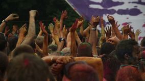 Crowd young people covered in colored powder paint, dancing. Stock footage stock footage