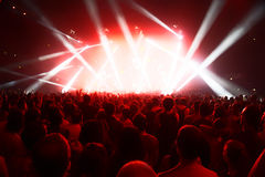Crowd of young people in front of bright stage lights royalty free stock image