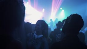 Crowd of young people in halloween costumes spending time at night club party. Flashing lights stock video footage