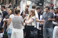 A crowd of young people talking to each other around a beer pub Stock Photography