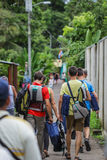Crowd of young people with their bagpacks and life vests are walking up towards jungles. Group op tourists heading towards adventurous tour in the jungle Stock Photos
