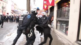 Crowd of young protesters chant at cop line. Special force police officers walk and run towards a crowd of young demonstrators in a downtown street stock video