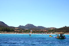 Crowded Beach In Golfo Di Marinella, Sardinia. Golfo Di Marinella, Sardinia, Italy, August 5, 2009 - Crowded beach and people practicing water sports - view from Royalty Free Stock Image