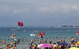 Crowded beach with pedal boats and parasail Royalty Free Stock Image