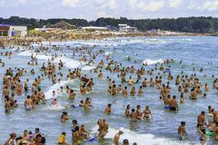 Crowded beach and people in the sea waves Stock Image