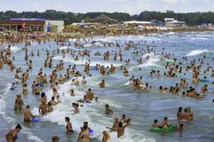 Crowded beach and people in the sea waves Stock Photo