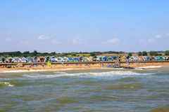 Crowded Beach at Southwold in UK. Southwold, UK - August 17, 2016 - Crowded beach at Southwold with a row of beach huts in the background Royalty Free Stock Image