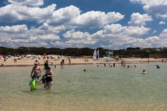 A crowded beach in summer as people enjoy swimming and playing in the ocean and sand. Anglesea, Australia - January 28, 2018. A crowded beach in summer as people Royalty Free Stock Photo