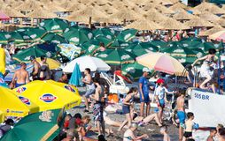 Crowded beach and a tourist boat. Canj, Montenegro - July 10, 2016: Crowded beach full of parasols, on a hot summer day. Some people are  embarking on a tourist Royalty Free Stock Photo