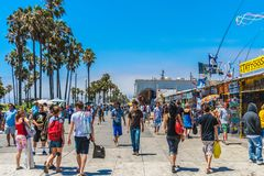 The Venice Beach crowded boardwalk in summer. The crowded boardwalk of Venice Beach in Los Angeles during a sunny and bright day of summer Stock Image