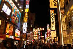 The crowded and bright Osaka at night. People, which are locals and tourists, flocked around the shopping area in Osaka. Not far from the famous icon `glico` Royalty Free Stock Photos