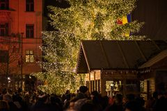 Abstract Christmas background. Crowded Christmas market in city center. Decorated Christmas tree with glowing lights and wooden huts full with gifts. Beautiful royalty free stock photo