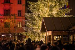Abstract Christmas background. Crowded Christmas market in city center. Decorated Christmas tree with glowing lights and wooden huts full with gifts. Beautiful royalty free stock photos