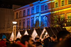 Abstract Christmas background. Crowded Christmas market in city center, decorated wooden huts with glowing lights. People enjoying event and searching for gifts stock photo