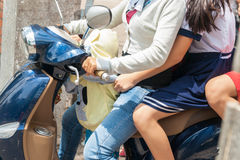 Crowded, closeup three people on moped in Asian city. Stock Images