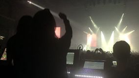 A crowded concert hall with scene stage lights, rock show performance, with people silhouette stock video