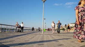 Crowded embankment on a summer day in Nizhny Novgorod. Adults, families with children walk in the summer by the river