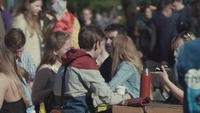 Crowded food area at summer festival, young people eating burgers. Crowded food area at summer festival in city park, young cheerful people in colorful clothes stock footage