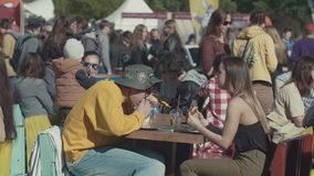 Crowded food court at summer festival, young people eating burgers. Crowded food court at summer festival in city park, young cheerful people in colorful clothes stock footage