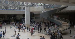 Crowded hall with spiral stairs in Louvre Pyramid stock video footage
