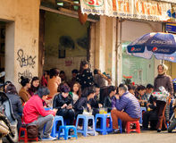 Crowded Hanoi Cafe, Vietnam. Men and women sit outside in low chairs at a crowded cafe in central Hanoi, northern Vietnam, known as the Old Quarter or the 36 royalty free stock image