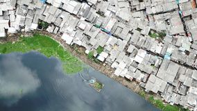 Crowded houses at the slum neighborhood. Top view of crowded houses at the slum neighborhood with an excavator on the lakeside at North Jakarta, Indonesia Stock Photo
