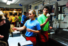 Crowded Ice Cream parlor. An ice cream parlor`s workers move quick to serve a summer crowd stock photos