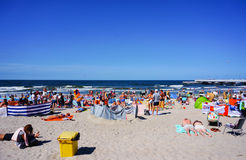 Crowded Kolobrzeg beach. KOLOBRZEG, POLAND - JULY 23, 2015: Many people sitting and lying on sand at a beach on a sunny day Stock Photos