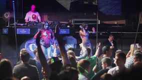Crowded party at night club, dancers perform on scene stock footage
