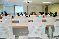 Crowded people attending the seminar event. Empty chairs in the classroom with blurred students in stock photos
