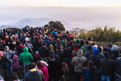 Crowded people are waiting for the first light in the dawn of new year`s day with mountain and fog in background at Tiger Hill. Stock Photography