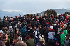 Crowded people are waiting for the first light in the dawn of new year`s day with mountain and fog in background at Tiger Hill. Royalty Free Stock Images
