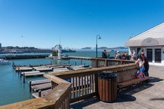 Pier 39 marina with yachts and people walking around. Sea lions on a wooden pontoon. Crowded Pier 39 in San Francisco USA Stock Photo